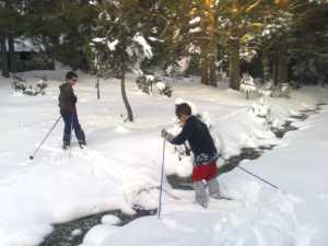 Niños cruzando un riachuelo con esquís de fondo